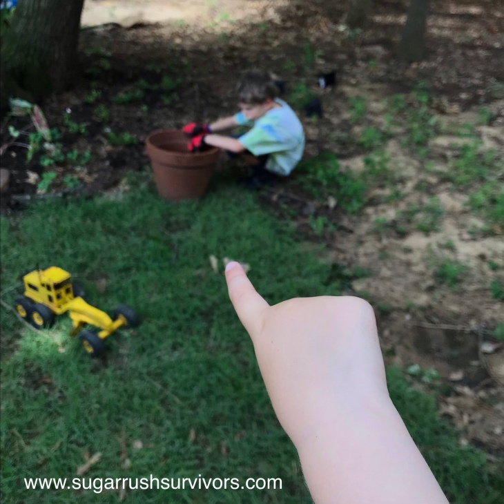 In the foreground a child's finger points to a young boy, blurred, in the background. The boy is crouched on the grass next to a large flowerpot. His posture is slouching and pouty. His arms rest on the flowerpot rim. A toy yellow tractor rests on the grass.