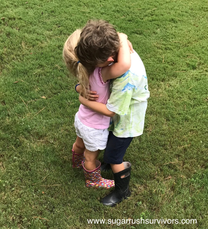 A little boy and little girl both in t-shirts, shorts, and rain boots, hug on a green lawn.